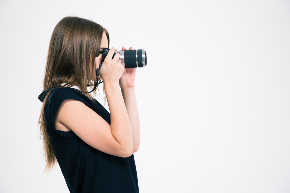 Side view portrait of a young woman making photo on camera isolated on a white background